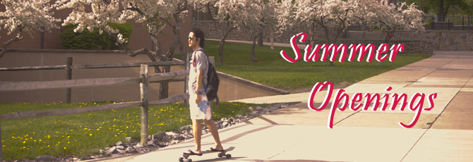 Photo of young man skateboarding in front of blossoming trees.